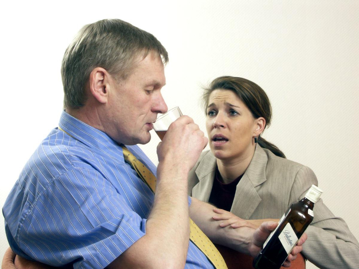 Женщина пытается остановить пьющего мужа