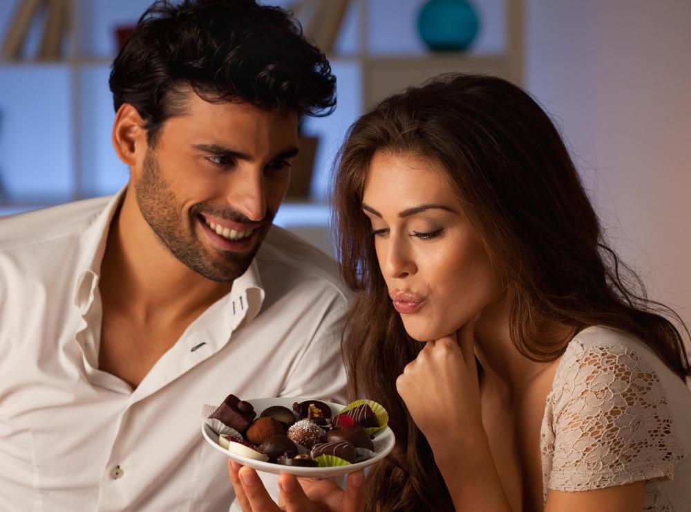 Мужчина угощает девушку шоколадом