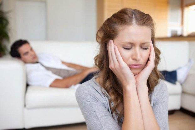 Женщина грустит, мужчина лежит на диване