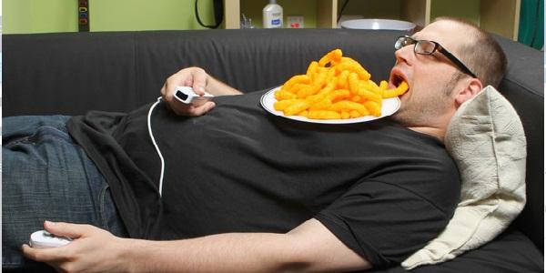 Безработный мужчина лежит на диване с едой