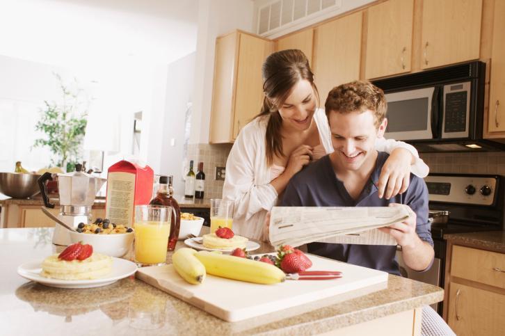 Муж смотрит газету, жена ему помогает и стоит чуть сзади