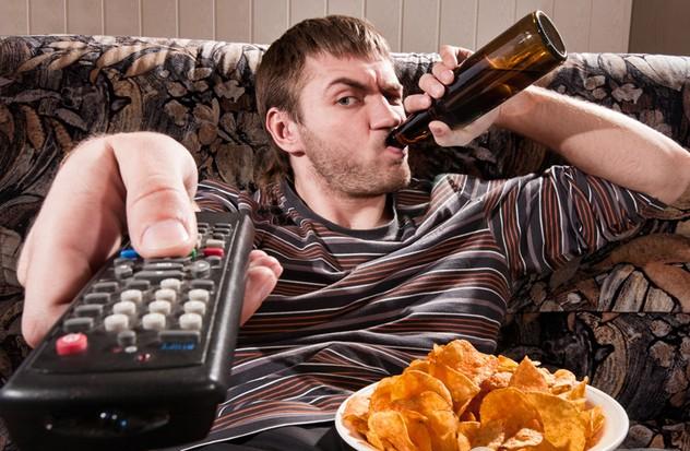 Мужчина перед телевизором пьет пиво