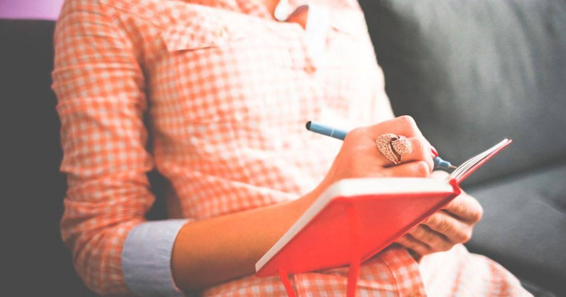 Рука пишет в красной книжке