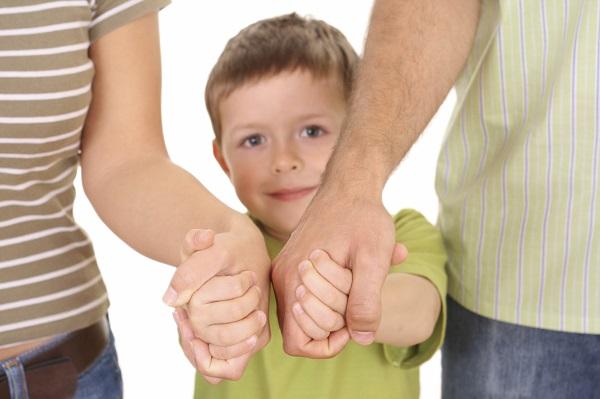 Ребенка держат за руки